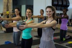Donne adatte che eseguono allungando esercizio con la palla di forma fisica nella palestra Immagini Stock Libere da Diritti