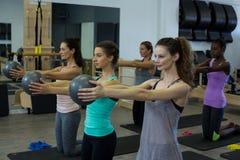 Donne adatte che eseguono allungando esercizio con la palla di forma fisica nella palestra Fotografia Stock Libera da Diritti