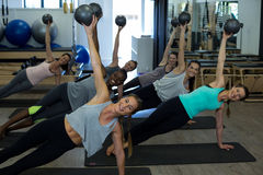 Donne adatte che eseguono allungando esercizio con la palla di forma fisica nella palestra Immagini Stock