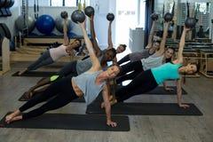 Donne adatte che eseguono allungando esercizio con la palla di forma fisica nella palestra Fotografia Stock