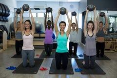 Donne adatte che eseguono allungando esercizio con la palla di forma fisica nella palestra Immagine Stock Libera da Diritti