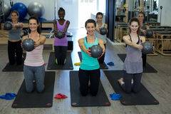 Donne adatte che eseguono allungando esercizio con la palla di forma fisica nella palestra Immagine Stock