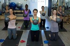 Donne adatte che eseguono allungando esercizio con la palla di forma fisica nella palestra Fotografie Stock Libere da Diritti
