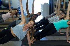 Donne adatte che eseguono allungando esercizio nella palestra Immagini Stock Libere da Diritti