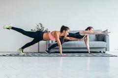 Donne adatte che fanno un allenamento di esercizio della plancia della gamba della mano una a casa Immagine Stock
