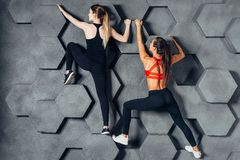 Donne adatte che posano come uno scalatore che appende sulla parete decorativa immagini stock libere da diritti