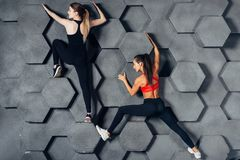 Donne adatte che posano come uno scalatore che appende sulla parete decorativa immagine stock