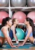 Donne allegre che fanno allungando esercizio di forma fisica Immagini Stock