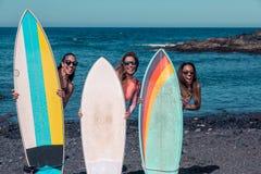 Donne allegre che stanno con i bordi sulla spiaggia immagine stock libera da diritti