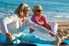 Donne anziane che fanno allungando gli esercizi sulla spiaggia. Fotografia Stock