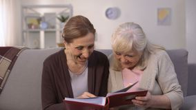 Donne anziane che guardano attraverso l'album in famiglia delle vecchie foto, memorie di piacere stock footage