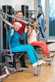 Donne anziane felici alla palestra assistita dall'istruttore Fotografie Stock Libere da Diritti