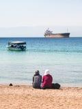 Donne arabe sulla spiaggia urbana nel giorno di inverno soleggiato Fotografia Stock