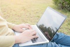 Donne asiatiche che per mezzo del computer portatile su prato inglese verde Fotografia Stock
