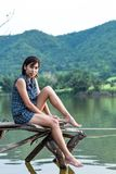 Donne asiatiche che si siedono su un ponte di legno, la montagna del fondo fotografia stock libera da diritti