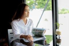 Donne asiatiche che sorridono e che leggono un libro per rilassamento al caffè Fotografie Stock