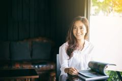 Donne asiatiche che sorridono e che leggono un libro per rilassamento al caffè Fotografia Stock