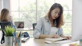 Donne asiatiche di servizio di assistenza al cliente che usando il email del cliente di risposta del computer sullo scrittorio video d archivio