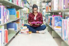 Donne asiatiche nella lettura delle biblioteche qualcosa in un libro e scegliere un libro in una biblioteca fotografie stock libere da diritti
