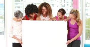 Donne atletiche sorridenti che indicano uno spazio della copia stock footage