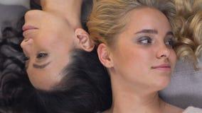 Donne attraenti con la menzogne riccia dei capelli testa a testa, la bellezza e la gioventù, skincare stock footage