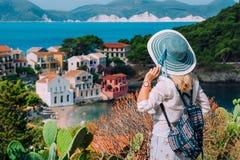 Donne bionde turistiche con il cappello del sole nel piccolo villaggio variopinto sveglio di Asso Kefalonia, Grecia immagine stock libera da diritti