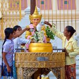 Donne birmane che versano acqua sopra la testa di Buddha a Shwedagon Paya, Myanmar Immagini Stock