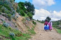 Donne boliviane in vestiti tradizionali sulla via Isola del Sun, Bolivia Fotografia Stock