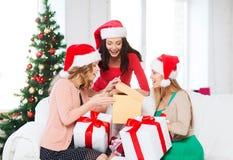 Donne in cappelli dell'assistente di Santa con molti contenitori di regalo Fotografia Stock