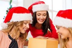 Donne in cappelli dell'assistente di Santa con molti contenitori di regalo Fotografia Stock Libera da Diritti