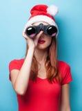 Donne in cappello di natale con binoculare Immagine Stock