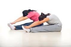 Donne che allungano i piedini e le braccia alla ginnastica Fotografia Stock Libera da Diritti