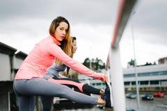 Donne che allungano le gambe prima dell'allenamento urbano all'aperto Immagine Stock