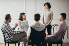 Donne che ascoltano lo pshychologist nel corso della riunione del gruppo di appoggio immagine stock