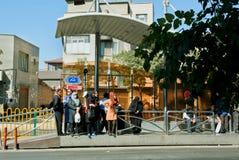 Donne che aspettano l'autobus alla fermata dell'autobus fotografie stock