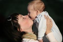 Donne che baciano il suo bambino Fotografie Stock