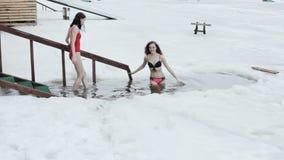 Donne che bagnano nel foro del ghiaccio archivi video