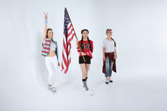 Donne che camminano con la bandiera americana isolata su bianco, concetto di festa dell'indipendenza Fotografia Stock Libera da Diritti