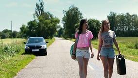 Donne che camminano sulla strada con la scatola metallica arrugginita a disposizione stock footage