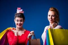 Donne che comperano con i lotti delle borse sul blu Immagini Stock Libere da Diritti