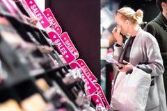 Donne che comprano e che provano i cosmetici in un deposito di bellezza fotografie stock