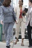 Donne che comunicano mentre camminando dall'ufficio. Immagini Stock