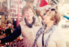 Donne che considerano le decorazioni al contatore del mercato di Natale Fotografie Stock