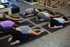 Donne che eseguono allungando esercizio sulla stuoia di esercizio Immagini Stock Libere da Diritti