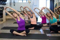 Donne che eseguono allungando esercizio sulla stuoia di esercizio Fotografie Stock