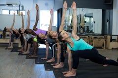 Donne che eseguono allungando esercizio sulla stuoia di esercizio Fotografie Stock Libere da Diritti