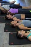 Donne che eseguono allungando esercizio sulla stuoia di esercizio Immagine Stock
