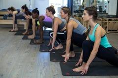 Donne che eseguono allungando esercizio sulla stuoia di esercizio Fotografia Stock