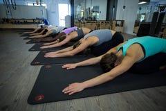 Donne che eseguono allungando esercizio sulla stuoia di esercizio Immagine Stock Libera da Diritti
