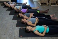 Donne che eseguono allungando esercizio sulla stuoia di esercizio Fotografia Stock Libera da Diritti